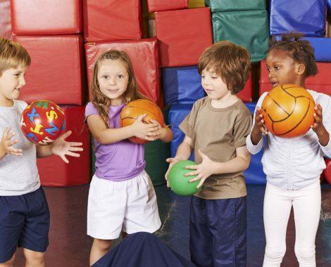 Kinder spielen mit verschiedenen Bällen in der Turnhalle einer Vorschule